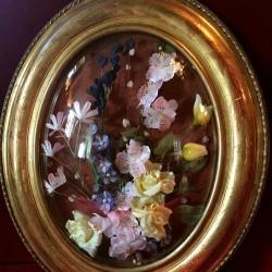 Cadre ovale doré, verre bombé, fleurs artificielles.