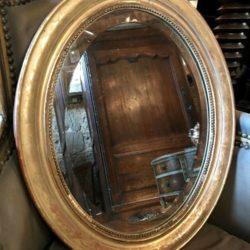 Miroir ovale biseauté cadre stuc doré