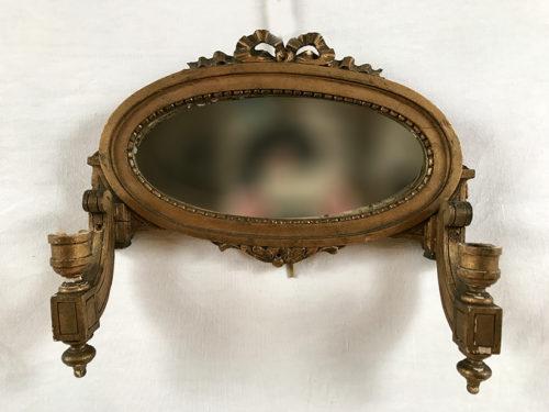 Applique miroir en bois doré portant deux bougeoirs de style Louis XVI